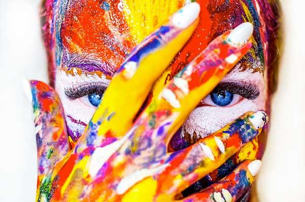 visage peint de multiple couleurs avec main qui cache sauf les yeux bleus